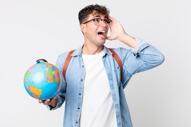 Jonge knappe man voelt zich gelukkig, opgewonden en verrast. student met een wereldbolkaart