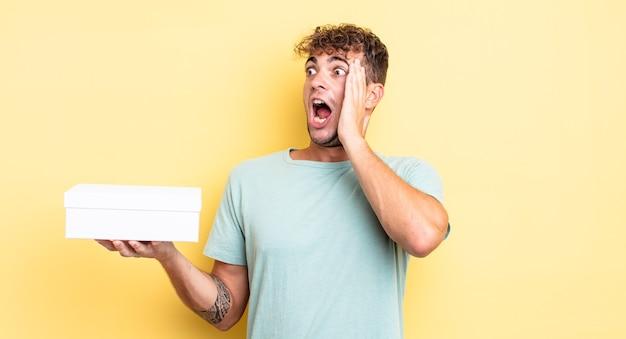 Jonge knappe man voelt zich gelukkig, opgewonden en verrast. witte doos concept
