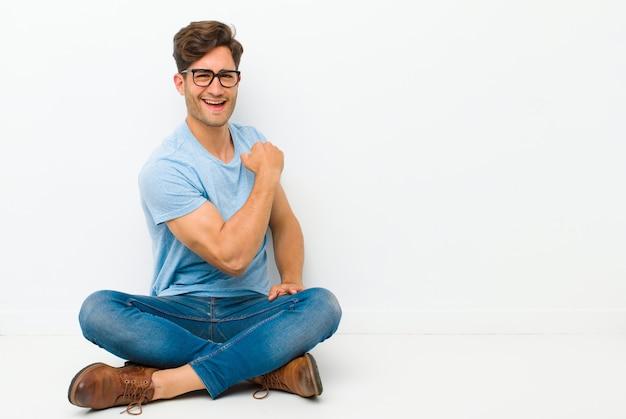 Jonge knappe man voelt zich gelukkig, tevreden en krachtig, buigt fit en gespierde biceps, ziet er sterk uit na de sportschool op de vloer zitten