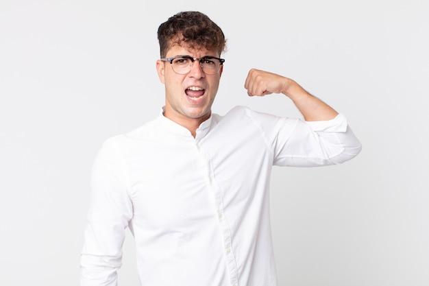 Jonge knappe man voelt zich gelukkig, tevreden en krachtig, buigt fit en gespierde biceps, ziet er sterk uit na de sportschool