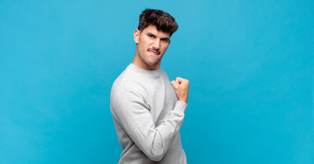 Jonge knappe man voelt zich gelukkig, tevreden en krachtig, buigt fit en gespierde biceps, ziet er sterk uit voor de sportschool