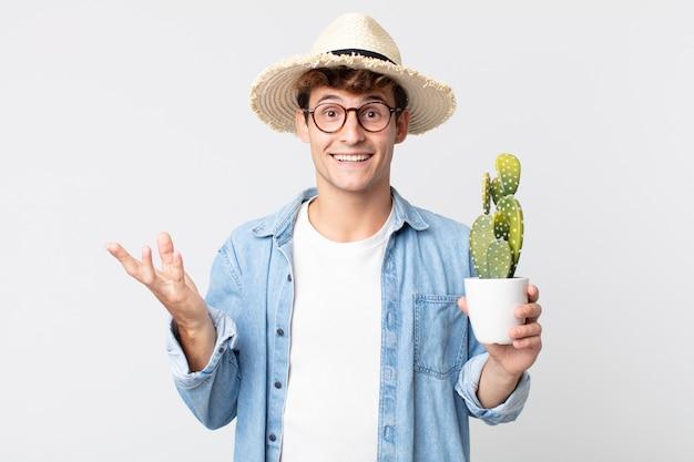 Jonge knappe man voelt zich gelukkig, verrast en realiseert een oplossing of idee. boer met een decoratieve cactus