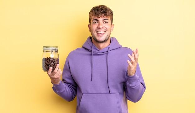 Jonge knappe man voelt zich gelukkig, verrast en realiseert een oplossing of idee. koffiebonen concept