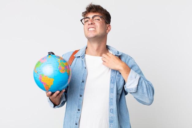 Jonge knappe man voelt zich gestrest, angstig, moe en gefrustreerd. student met een wereldbolkaart