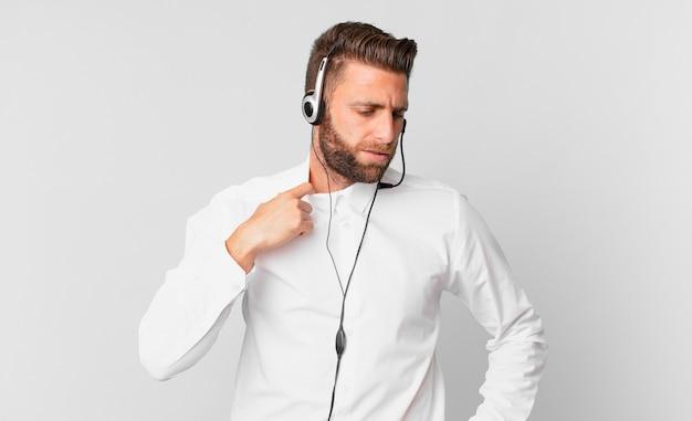 Jonge knappe man voelt zich gestrest, angstig, moe en gefrustreerd. telemarketing concept