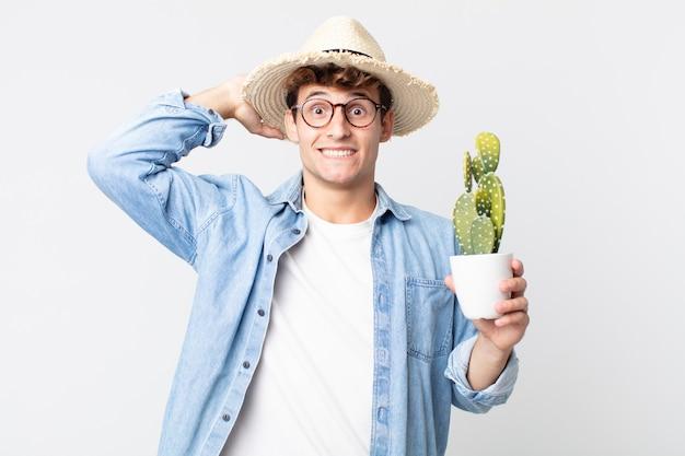 Jonge knappe man voelt zich gestrest, angstig of bang, met de handen op het hoofd. boer met een decoratieve cactus