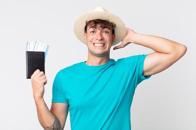 Jonge knappe man voelt zich gestrest, angstig of bang, met de handen op het hoofd. reiziger met zijn paspoort