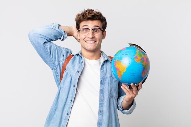 Jonge knappe man voelt zich gestrest, angstig of bang, met de handen op het hoofd. student met een wereldbolkaart