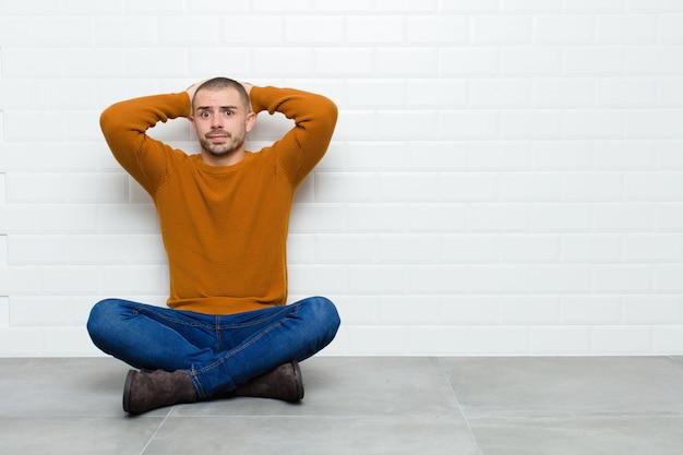 Jonge knappe man voelt zich gestrest, bezorgd, angstig of bang, met de handen op het hoofd, in paniek bij een fout zittend op de vloer