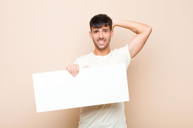 Jonge knappe man voelt zich gestrest, bezorgd, angstig of bang, met handen op het hoofd, in paniek bij vergissing met een bordje