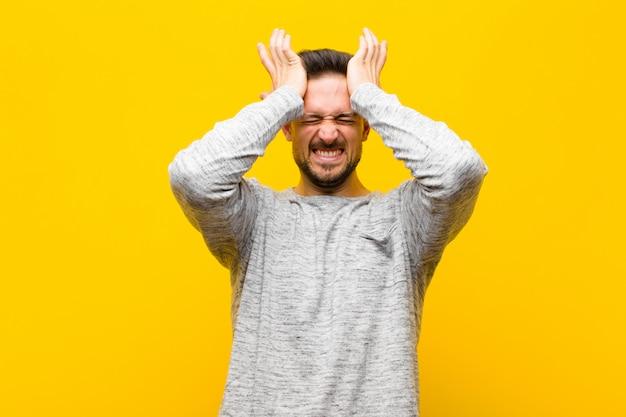 Jonge knappe man voelt zich gestrest en angstig, depressief en gefrustreerd met een hoofdpijn, beide handen opheffend om tegen de oranje muur te gaan