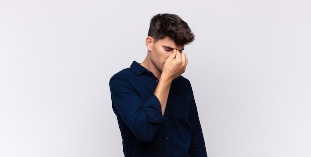 Jonge knappe man voelt zich gestrest, ongelukkig en gefrustreerd, raakt het voorhoofd aan en lijdt aan migraine of ernstige hoofdpijn