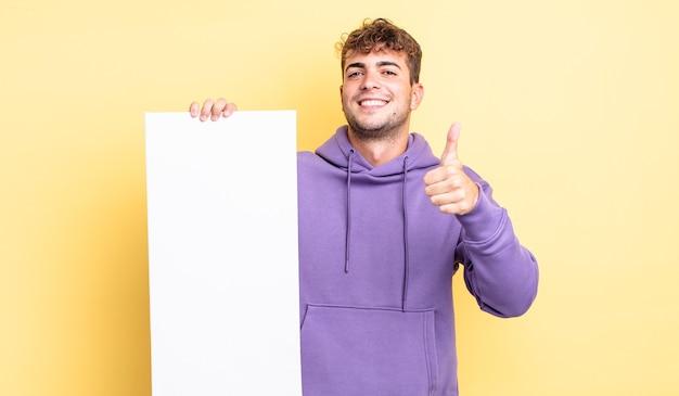 Jonge knappe man voelt zich trots, positief glimlachend met duimen omhoog. kopieer ruimteconcept