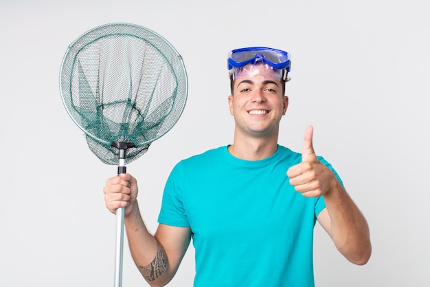 Jonge knappe man voelt zich trots, positief glimlachend met duimen omhoog met bril en visnet