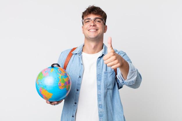 Jonge knappe man voelt zich trots, positief glimlachend met duimen omhoog. student met een wereldbolkaart