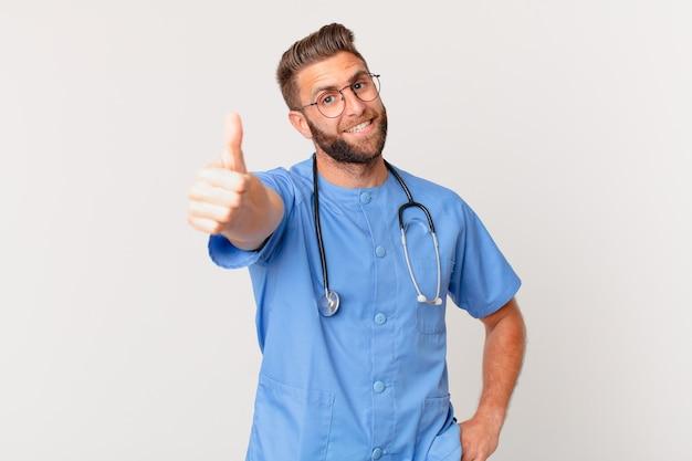 Jonge knappe man voelt zich trots, positief glimlachend met duimen omhoog. verpleegster concept