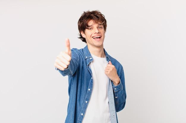 Jonge knappe man voelt zich trots, positief glimlachend met duimen omhoog