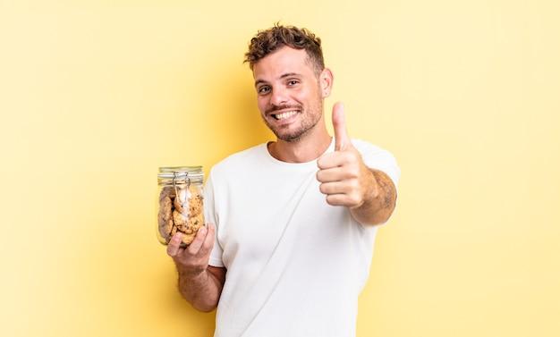 Jonge knappe man voelt zich trots, positief lachend met duimen omhoog cookies fles concept