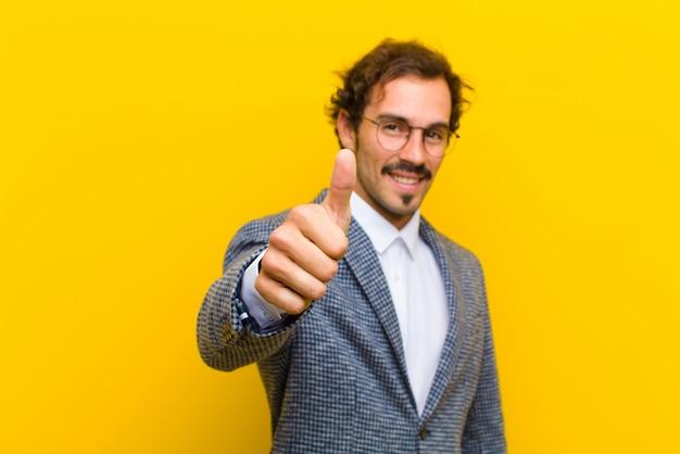 Jonge knappe man voelt zich trots, zorgeloos, zelfverzekerd en gelukkig, glimlachend positief met duimen omhoog tegen oranje muur