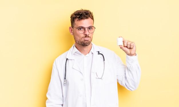 Jonge knappe man voelt zich verdrietig en zeurt met een ongelukkige blik en huilt. arts pillen fles concept