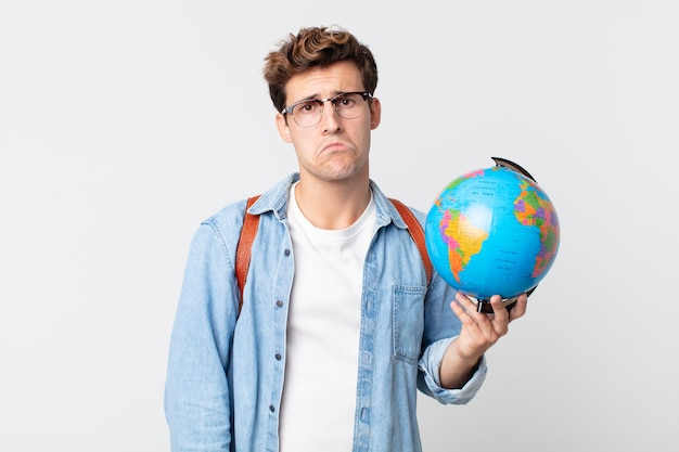 Jonge knappe man voelt zich verdrietig en zeurt met een ongelukkige blik en huilt. student met een wereldbolkaart