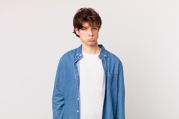 Jonge knappe man voelt zich verdrietig en zeurt met een ongelukkige blik en huilt