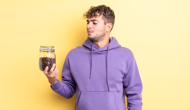 Jonge knappe man voelt zich verdrietig, overstuur of boos en kijkt opzij. koffiebonen concept