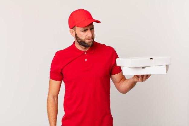 Jonge knappe man voelt zich verdrietig, overstuur of boos en kijkt opzij. pizza bezorgconcept