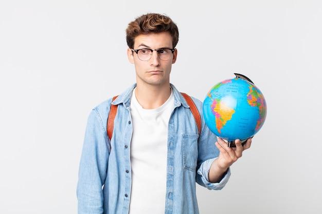 Jonge knappe man voelt zich verdrietig, overstuur of boos en kijkt opzij. student met een wereldbolkaart