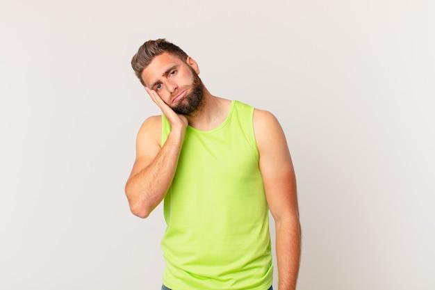 Jonge knappe man voelt zich verveeld, gefrustreerd en slaperig na een vermoeiende. fitnessconcept