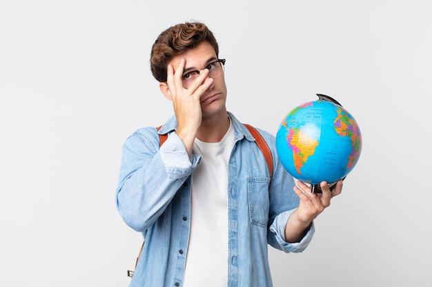 Jonge knappe man voelt zich verveeld, gefrustreerd en slaperig na een vermoeiende student met een wereldbolkaart