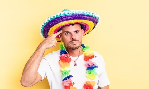 Jonge knappe man voelt zich verward en verbaasd en laat zien dat je gek bent. mexicaans feestconcept