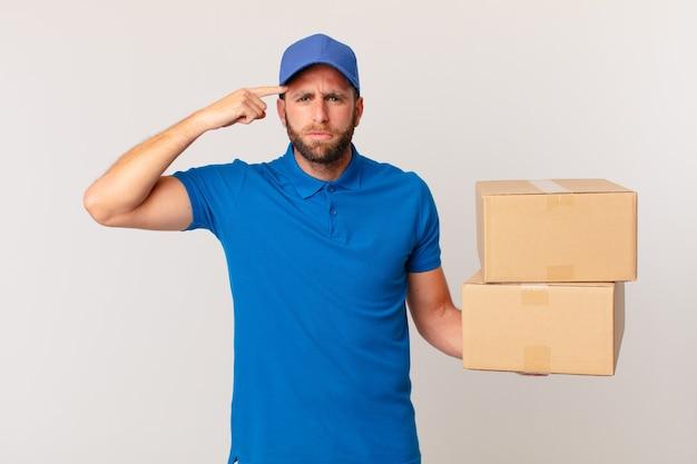 Jonge knappe man voelt zich verward en verbaasd en laat zien dat je gek bent. pakket leveren concept