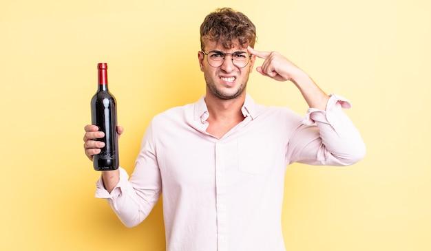 Jonge knappe man voelt zich verward en verbaasd en laat zien dat je gek bent. wijnfles concept