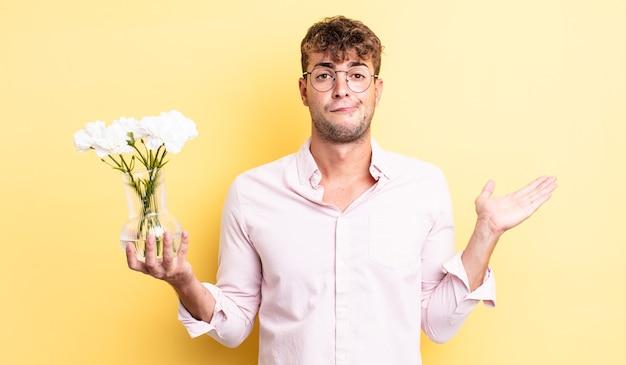 Jonge knappe man voelt zich verward en verward en twijfelt. bloemen concept