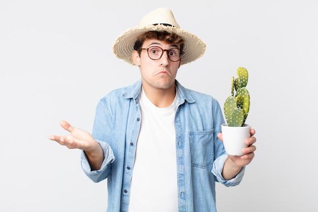 Jonge knappe man voelt zich verward en verward en twijfelt. boer met een decoratieve cactus