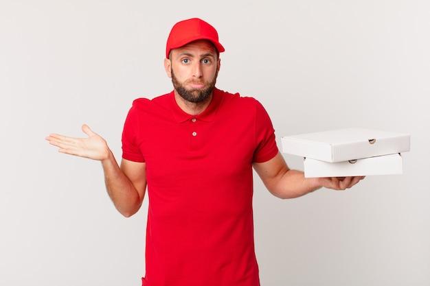 Jonge knappe man voelt zich verward en verward en twijfelt. pizza bezorgconcept