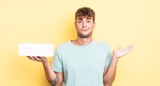 Jonge knappe man voelt zich verward en verward en twijfelt. witte doos concept