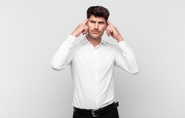 Jonge knappe man voelt zich verward of twijfelt, concentreert zich op een idee, denkt hard na, zoekt ruimte aan de zijkant te kopiëren