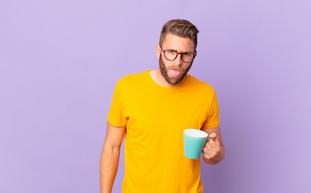 Jonge knappe man voelt zich walgelijk en geïrriteerd en tong uit. en een koffiemok vasthouden
