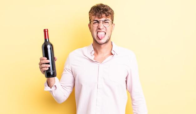 Jonge knappe man voelt zich walgelijk en geïrriteerd en tong uit. wijnfles concept