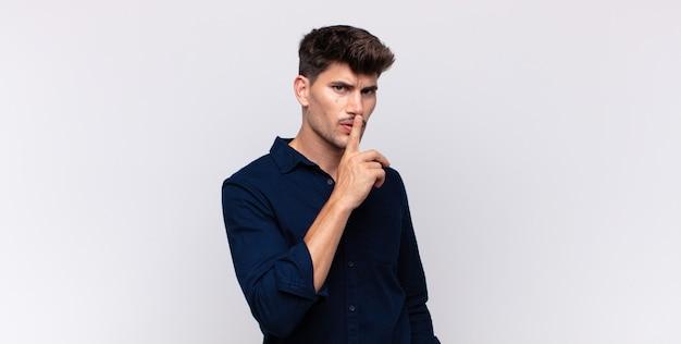 Jonge knappe man vraagt om stilte en stilte, gebaart met de vinger voor de mond, zegt shh of houdt een geheim
