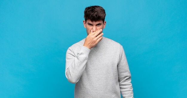 Jonge knappe man walgt en houdt zijn neus vast om te voorkomen dat hij een vieze en onaangename stank ruikt