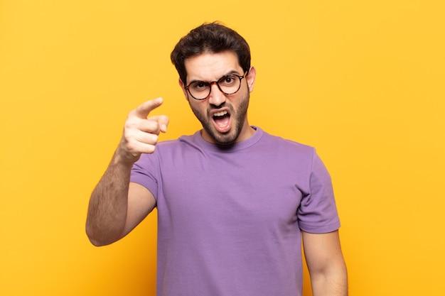 Jonge knappe man wijzend op camera met een boze agressieve uitdrukking op zoek als een woedende, gekke baas