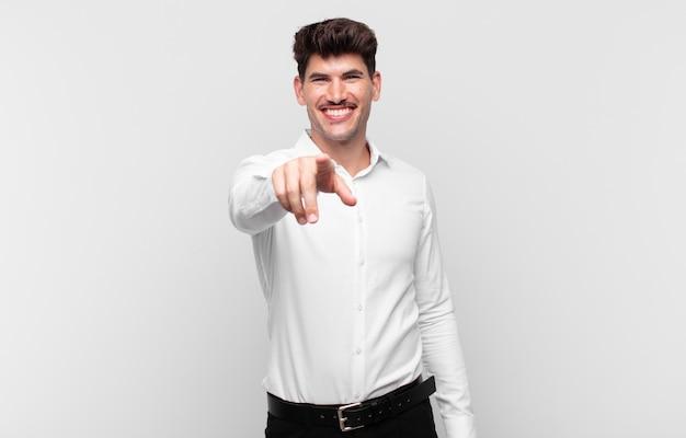 Jonge knappe man wijzend op camera met een tevreden, zelfverzekerde, vriendelijke glimlach, jou kiezen