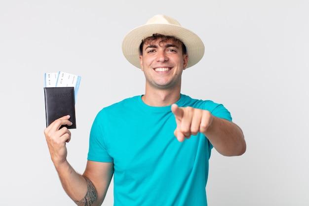 Jonge knappe man wijzend op de camera die jou kiest. reiziger met zijn paspoort