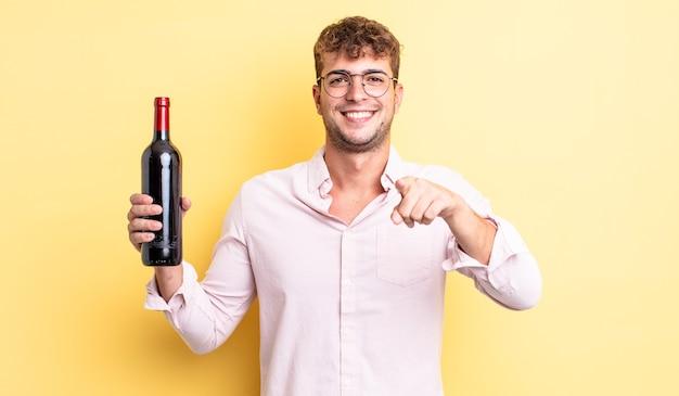 Jonge knappe man wijzend op de camera die jou kiest. wijnfles concept