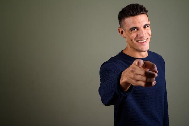 Jonge knappe man wijzende vinger op camera tegen gekleurde achtergrond