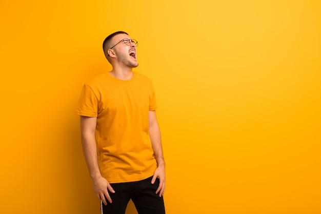 Jonge knappe man woedend schreeuwen, agressief schreeuwen, op zoek gestrest en boos tegen de vlakke muur
