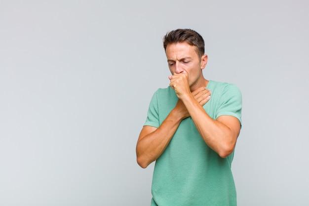 Jonge knappe man ziek met keelpijn en griepsymptomen, hoesten met bedekte mond